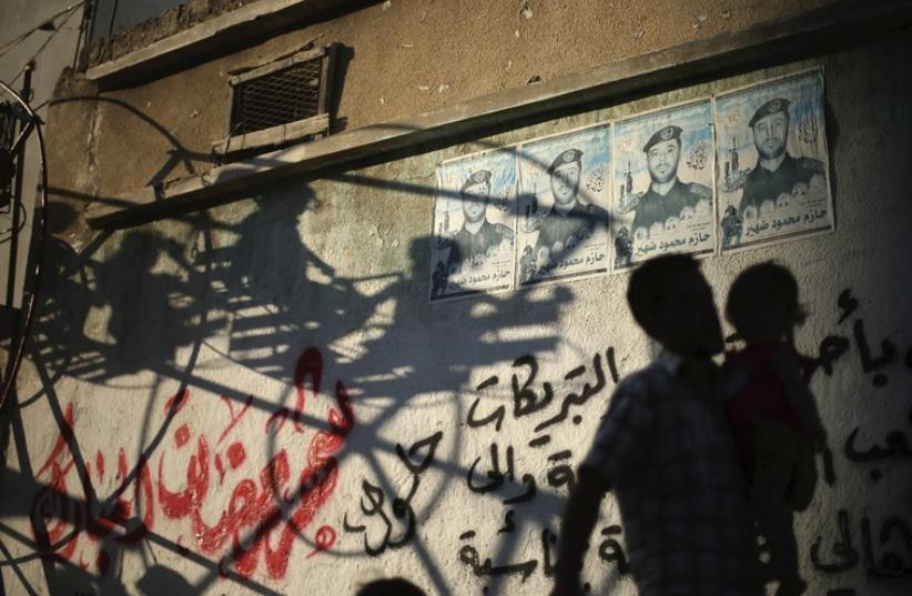 A PALESTINIAN man carries his son past graffiti on a building in the Gaza Strip. (photo credit: REUTERS)