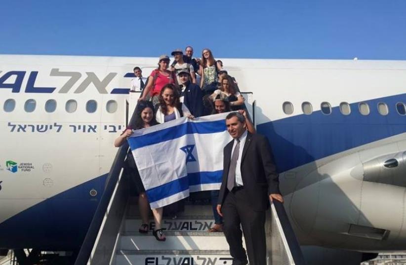 Zeev Elkin welcomes olim on the 53rd Nefesh B'Nefesh flight as it lands in Israel (photo credit: STEVE LINDE)