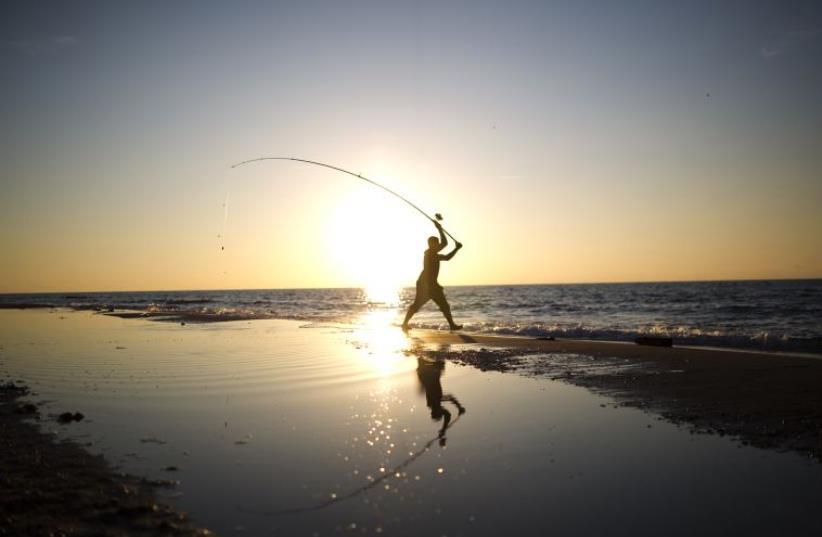 A man casts his fishing line in the Mediterranean Sea on Zikim beach, near Ashkelon (photo credit: REUTERS)