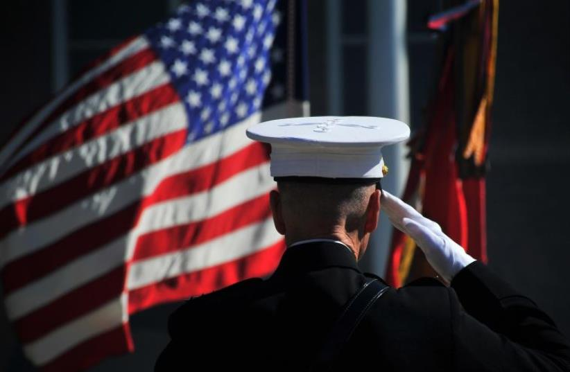 US Marine Corps Gen. James F. Amos, the outgoing commandant of the Marine Corps, salutes the colors during the passage of command ceremony at Marine Barracks Washington in Washington, DC (photo credit: US DEPARTMENT OF DEFENSE)