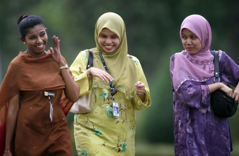 Ethnic Malays and an ethnic Indian share a light moment as they leave office after work in Putrajaya outside Kuala Lumpur. (photo credit: REUTERS)