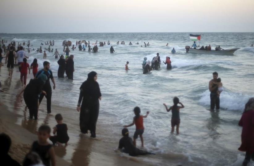 Palestinians enjoy the beach along the Mediterranean Sea in the northern Gaza Strip July 24, 2015.  (photo credit: REUTERS)