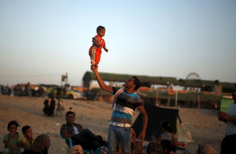 A Palestinian man lifts his daughter at beach along the Mediterranean Sea in the northern Gaza Strip July 24, 2015.  (photo credit: REUTERS)