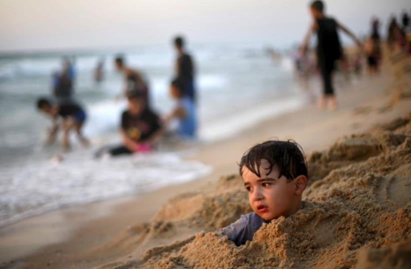 Palestinian boy buries himself in the sand at beach along the Mediterranean Sea in the northern Gaza Strip July 24, 2015.  (photo credit: REUTERS)