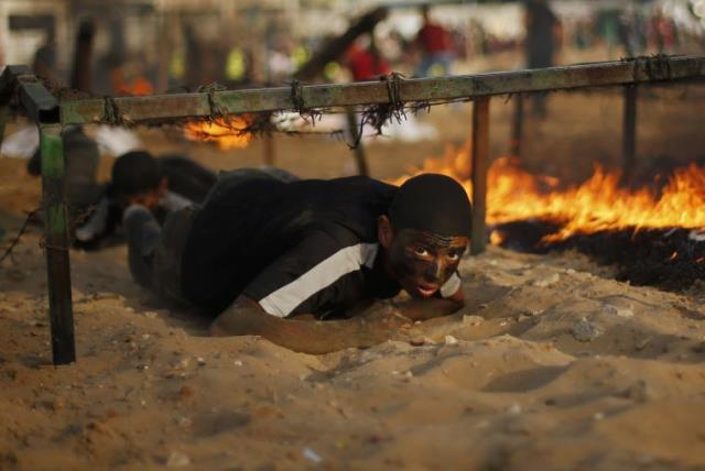 A young Palestinian crawls under an obstacle during a military-style graduation ceremony at a summer camp in Gaza (photo credit: REUTERS/MOHAMMED SALEM)