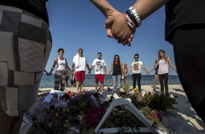 People hold hands as they pray in a circle around bouquets of flowers (photo credit: REUTERS)