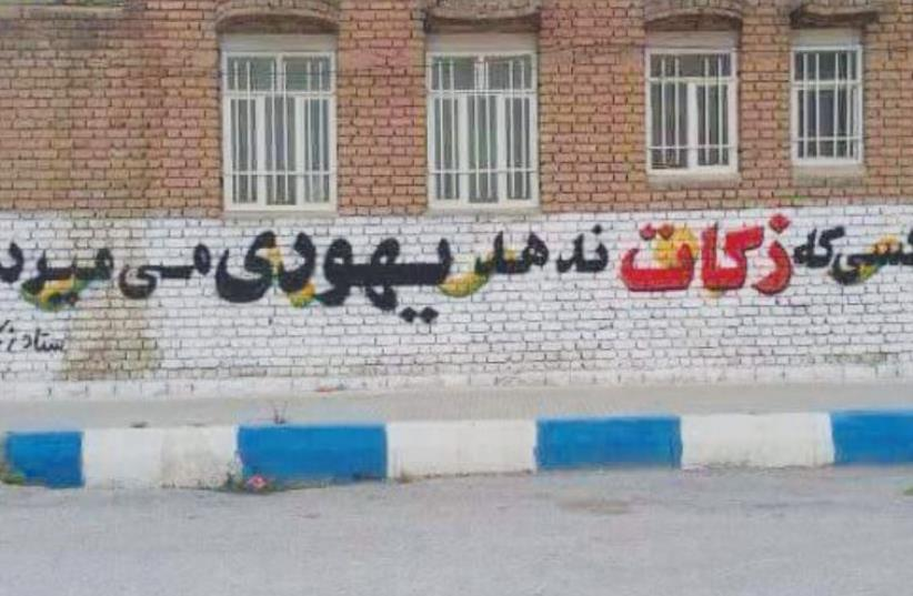 THIS GRAFFITI on a wall in Iran reads: 'He who does not give charity dies as a Jew' (photo credit: Courtesy)