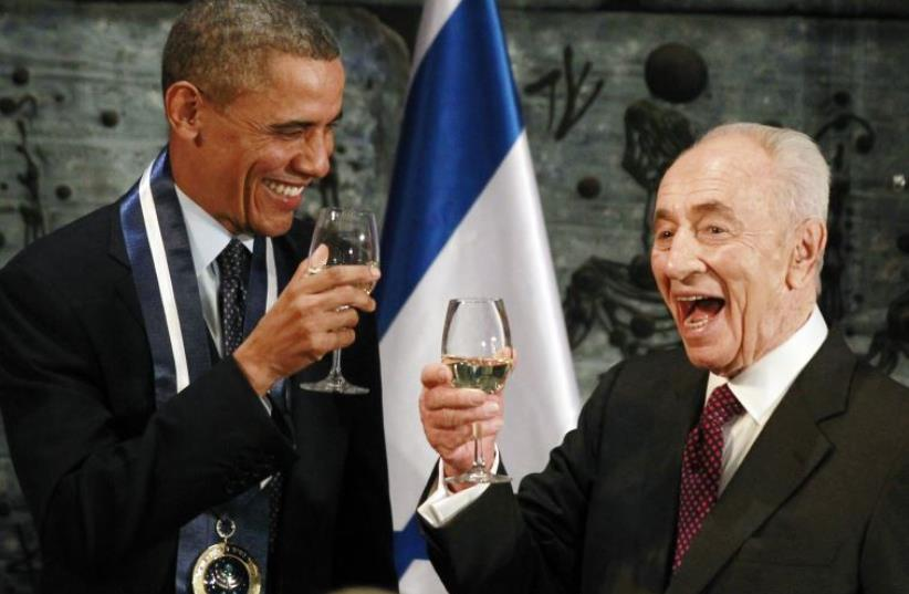 US President Barack Obama toasts with former president Shimon Peres after Obama was presented with the Presidential Medal of Distinction, Israel's highest civilian honor, in Jerusalem, March 21, 2013 (photo credit: REUTERS)