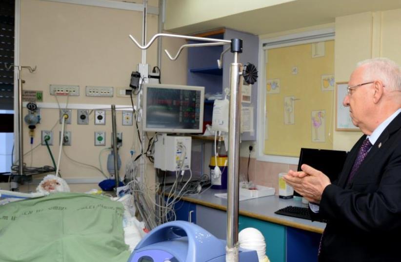 President Reuven Rivlin at the bedside of Ahmed Dawabsha, 4, at Sheba Medical Center in Tel Hashomer (photo credit: Mark Neiman/GPO)
