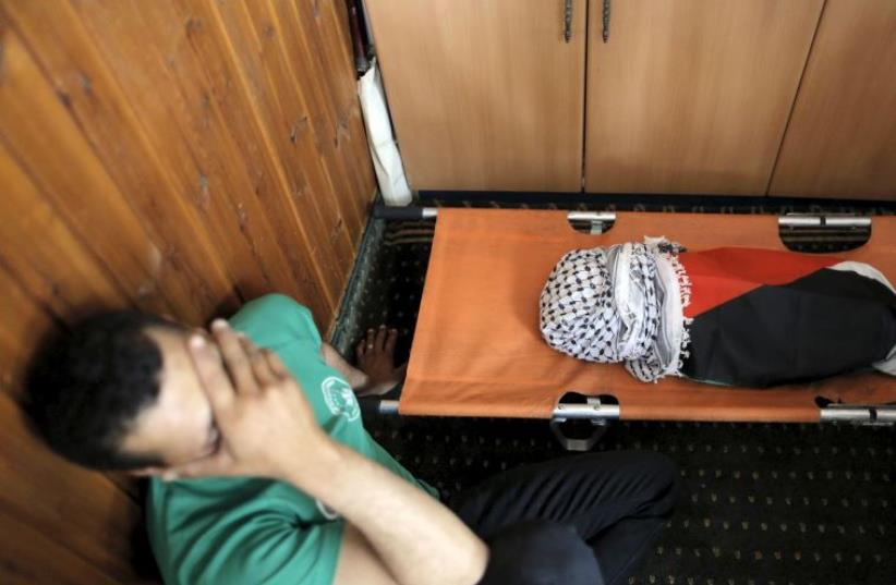 A mourner reacts next to the body of 18-month-old Palestinian baby Ali Dawabsha, who was killed after his family's house was set to fire in a suspected attack by Jewish extremists in Duma (photo credit: REUTERS)