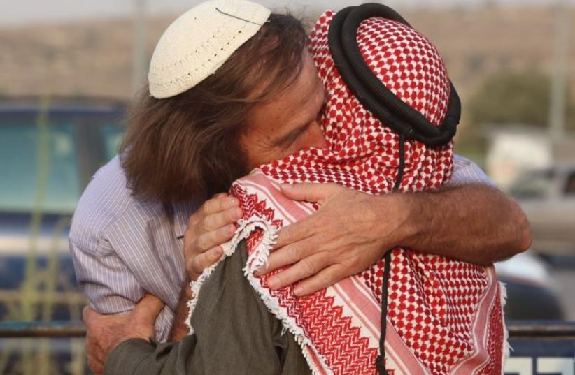 A rabbi and a sheikh embrace at a co-existence meeting (photo credit: MARC ISRAEL SELLEM)