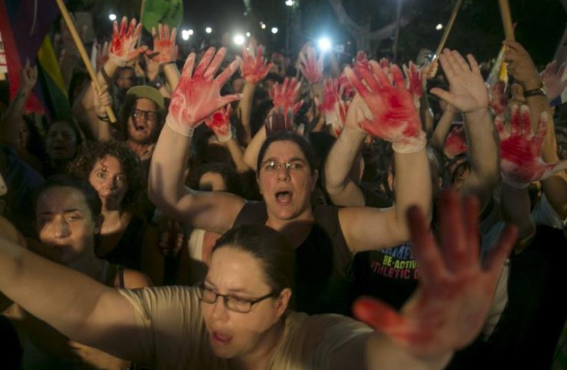 Protesters hold up gloves covered in red during a protest against the violence towards the gay community in Tel Aviv August 1, 2015 (photo credit: REUTERS)