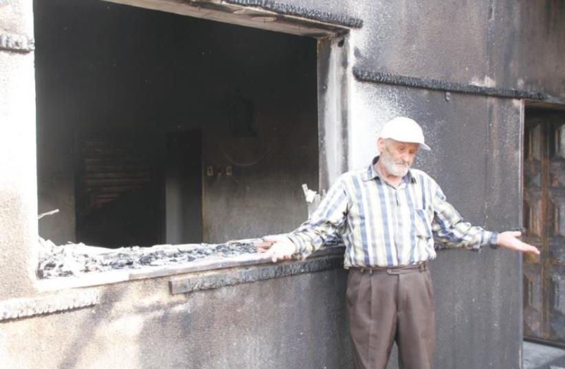 RASHID DAWABSHA stands outside his son Mamoun's torched home in the Arab village Duma on Sunday (photo credit: TOVAH LAZAROFF)