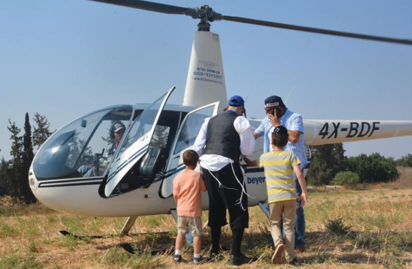 MOTTI FRIED (center) helps children from his organization Saad V'Marpe get into a helicopter for a ride as part of a recent week-long summer camp. (photo credit: SAAD V'MARPE)