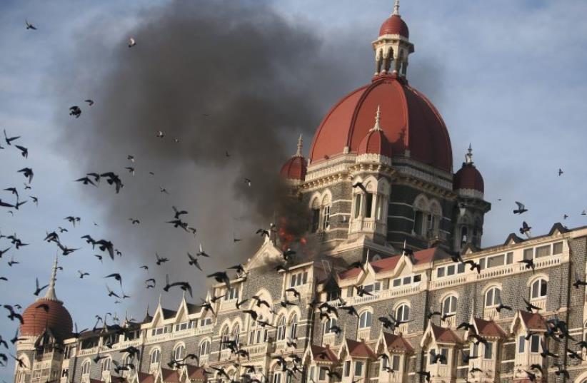 Pigeons fly near the burning Taj Mahal hotel in Mumbai November 27, 2008. (photo credit: REUTERS)
