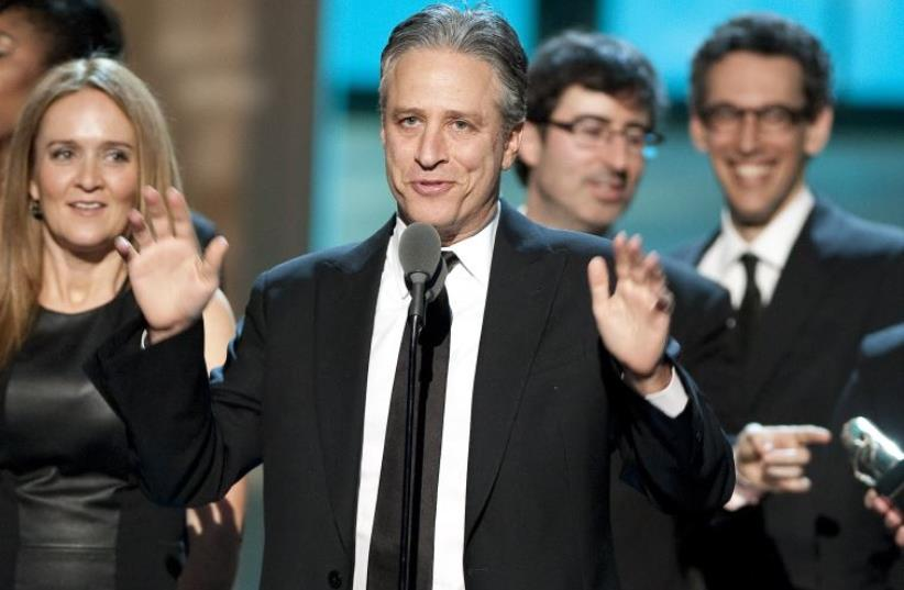 Talk show host Jon Stewart, flanked by his writers and correspondents, speaks after receiving the Best Late Night Comedy Series Award for his show (photo credit: REUTERS)
