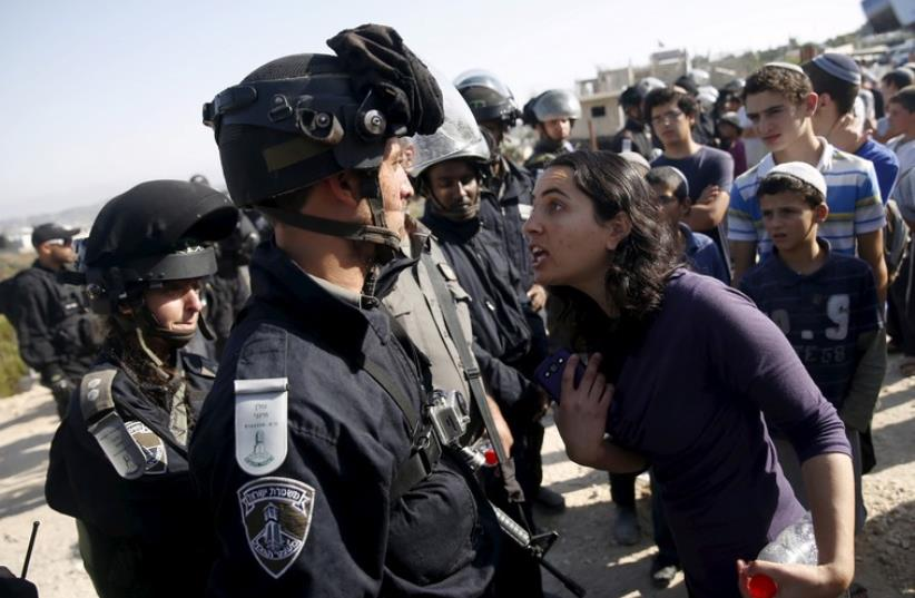 A young Jewish settler (R) speaks with an Israeli police officer near buildings slated for demolition in the West Bank Jewish settlement of Beit El (photo credit: REUTERS)