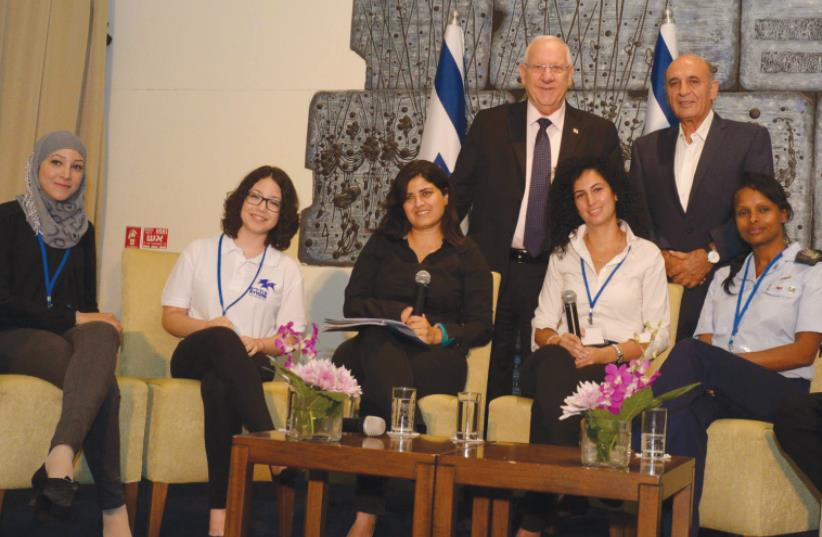 PRESIDENT REUVEN RIVLIN and former IDF chief of staff Shaul Mofaz (standing) join participants of the Atidim program during a celebration of the organization's 15th anniversary yesterday at the President's Residence in Jerusalem. (photo credit: HAIM ZACH/GPO)