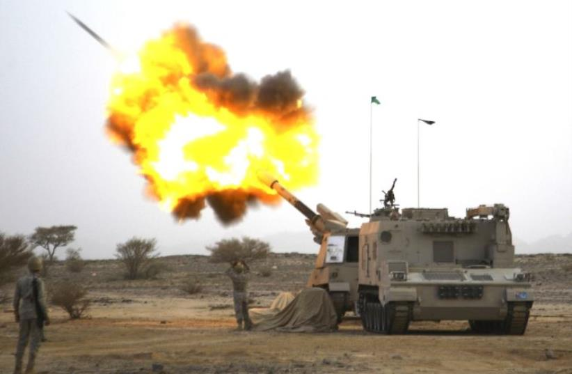 Saudi artillerymen at the border with Yemen fire at Houthi positions (photo credit: REUTERS)