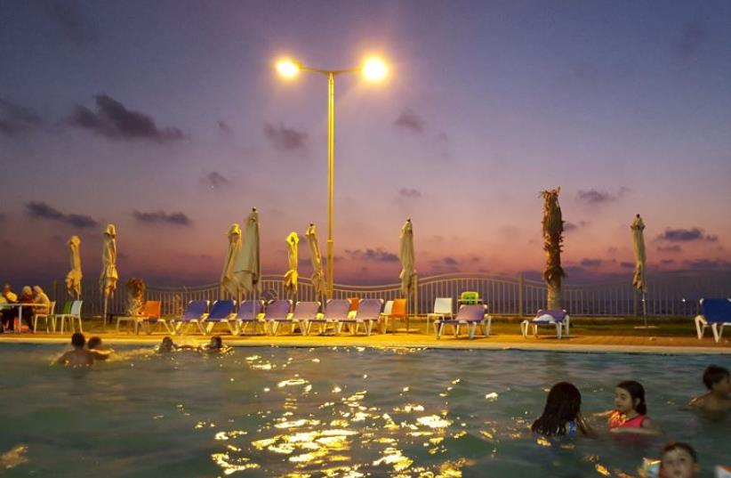 Palestinian children swim in a pool as they enjoy the warm weather with their families at the Blue Beach Resort in Gaza (photo credit: REUTERS)