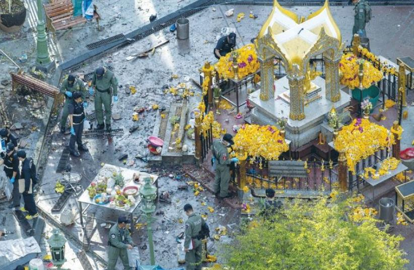 EXPERTS EXAMINE the scene of the explosion at the Erawan Shrine in Bangkok yesterday. (photo credit: REUTERS)