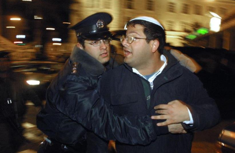 A policeman arrests Israeli right-wing activist Itamar Ben Gvir during a 'Peace Now' demonstration in Jerusalem (photo credit: GALI TIBBON / AFP)