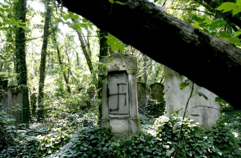 A spray-painted tombstone at a Jewish cemetery (photo credit: REUTERS)