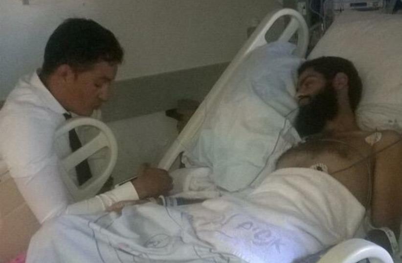 Muhammad Allan, with his lawyer, recovering in hospital (photo credit: MARUAN ABU FARIYA)
