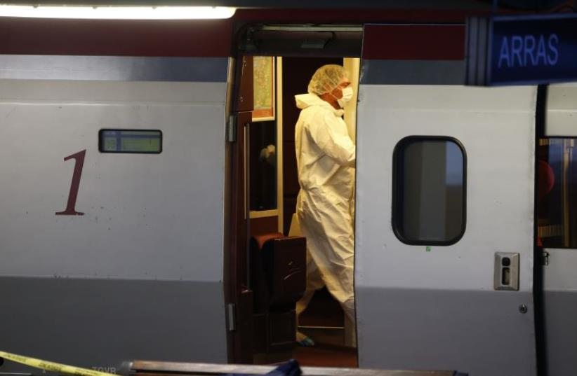 French investigating police in protective clothing collect clues inside the Thalys high-speed train where shots were fired in Arras (photo credit: REUTERS)