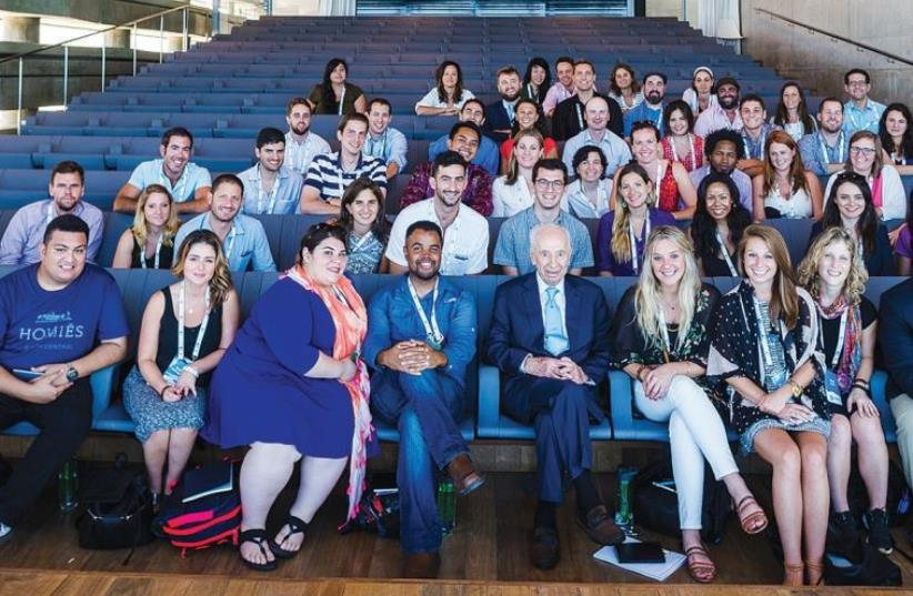 REALITY GLOBAL participants pose for a photograph with former president Shimon Peres ahead of his address to them at the Peres Peace Center in Tel Aviv yesterday (photo credit: NETANEL TOBIAS)