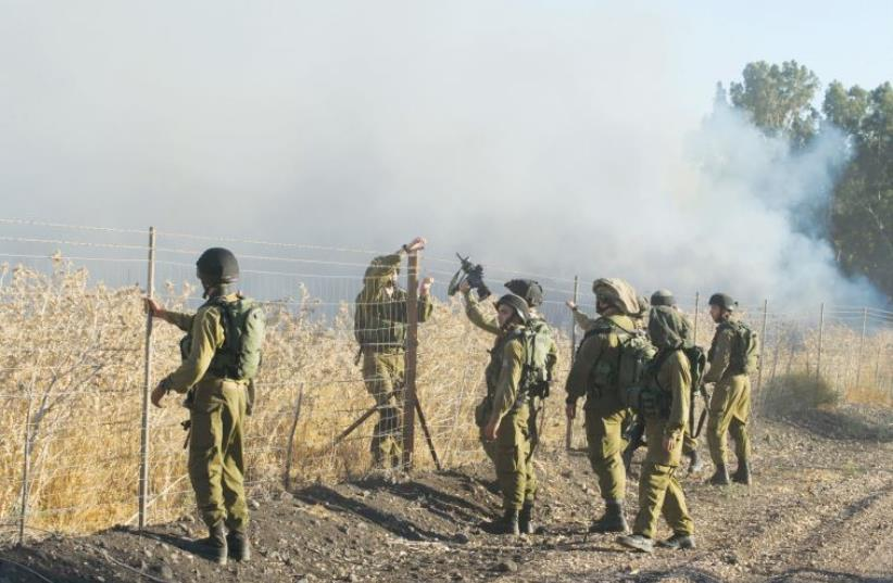 Soldiers fix a fence on the border with Lebanon while smoke billows in the background, from rockets fired from Syria (photo credit: REUTERS)