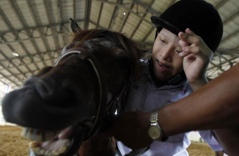 An autistic child plays with a horse during the Horse Therapy Special Children program at the Mounted Police Sub-Division in Bangkok (photo credit: REUTERS)