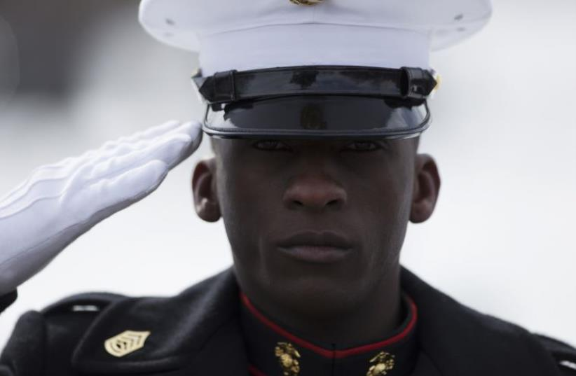 A Marine salutes the American flag during a wreath laying ceremony at the Marine Corps War Memorial in Washington (photo credit: UNITED STATES MARINE CORPS)