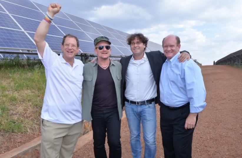 U2 LEAD SINGER BONO (second left) poses yesterday at the Gigawatt Global facility in Rwanda with (from left) company founder and president Yosef Abramowitz, co-founder Chaim Motzen and US Sen. Chris Coons (photo credit: GIGAWATT GLOBAL)