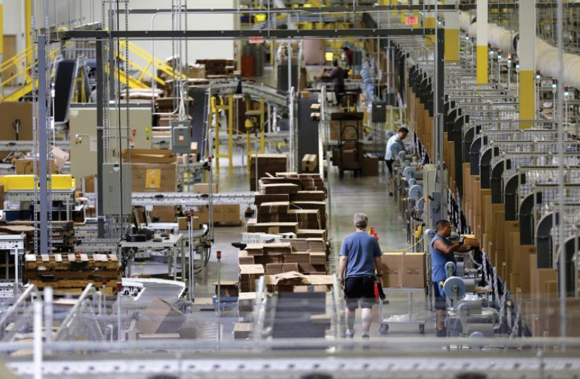 WORKERS SORT products at an Amazon Fulfillment Center in Tracy, California early this month (photo credit: REUTERS)