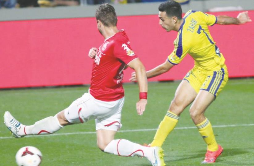 Maccabi Tel Aviv midfielder Eran Zahavi (right) kicking the ball during a match against Hapoel Tel Aviv (photo credit: ADI AVISHAI)