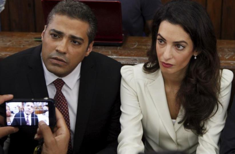 Al Jazeera television journalist Mohamed Fahmy (L) and his lawyer Amal Clooney look on before hearing the verdict at a court in Cairo (photo credit: REUTERS)
