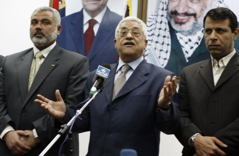 Palestinian president Abbas stands between PM Haniyeh and senior Fatah leader Dahlan in Gaza (photo credit: SUHAIB SALEM / REUTERS)