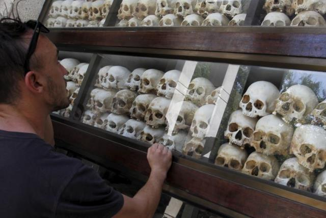 "A tourist looks at skulls and bones of more than 8,000 victims of the Khmer Rouge regime displayed at Choeung Ek, a ""Killing Fields"" site located on the outskirts of Phnom Penh July 2, 2015.  (photo credit: REUTERS)"