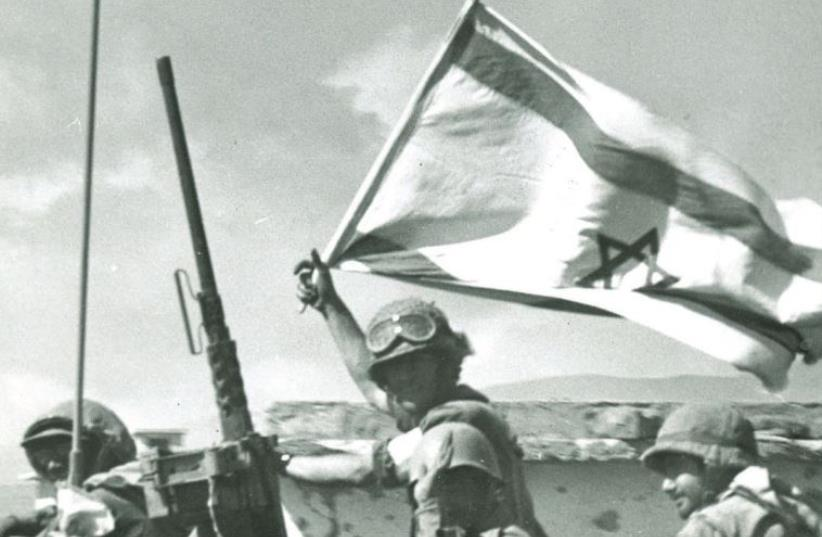 A soldier waves an Israeli flag on the Golan front during the Yom Kippur war. (photo credit: IDF SPOKESPERSON'S UNIT,JERUSALEM REPORT ARCHIVES)