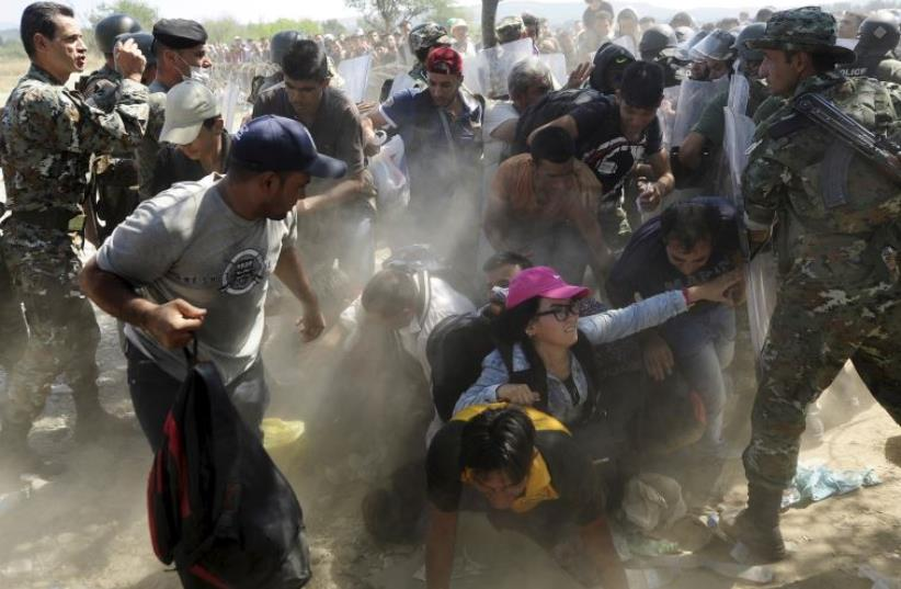 Migrants fall as they rush to cross into Macedonia after Macedonian police allowed a small group of people to pass through a passageway, as they try to regulate the flow of migrants at the Macedonian-Greek border  (photo credit: REUTERS)