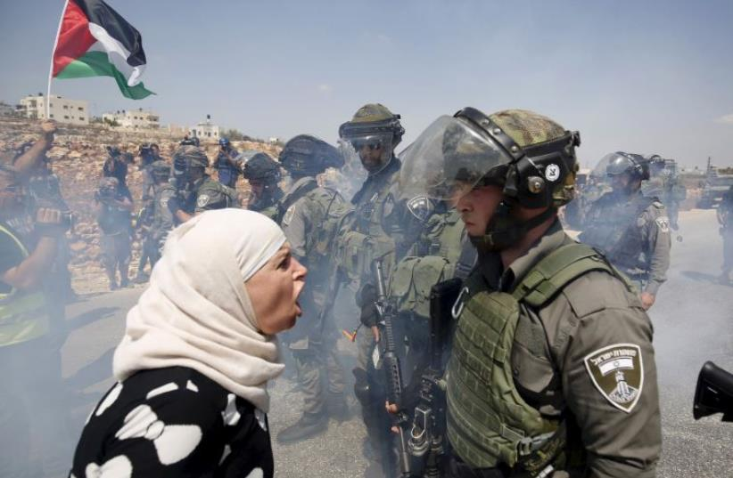 A Palestinian woman argues with an Israeli border policeman during a protest against Jewish settlements in the West Bank village of Nabi Saleh (photo credit: REUTERS)