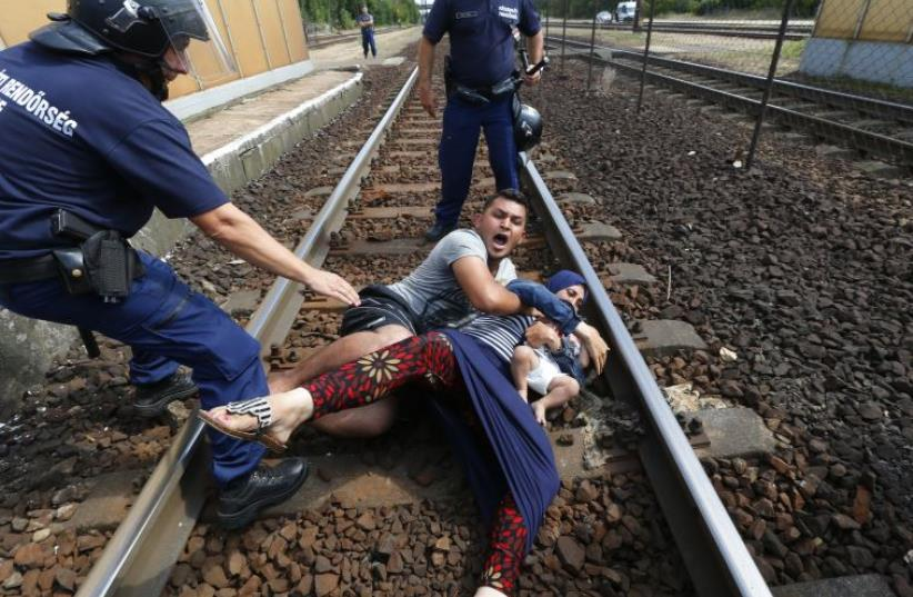 Hungarian policemen stand by the family of migrants as they wanted to run away at the railway station in the town of Bicske (photo credit: REUTERS)