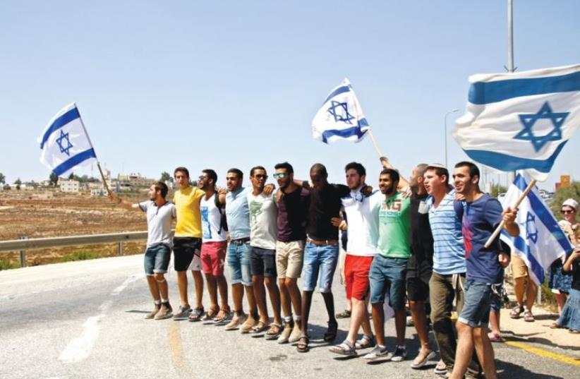 Right-wing Israeli demonstrators (bottom) express support for the IDF outside Halamish (photo credit: TOVAH LAZAROFF)