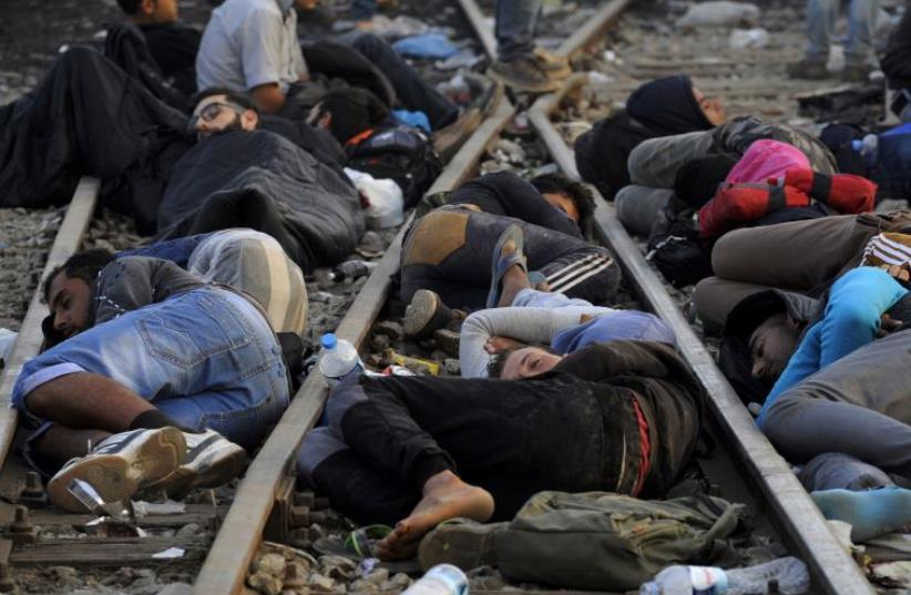 DATE IMPORTED: September 06, 2015 Refugees and migrants sleep on the railway tracks close to the borders of Greece with Macedonia, near the village of Idomeni, September 6, 2015.  (photo credit: REUTERS)