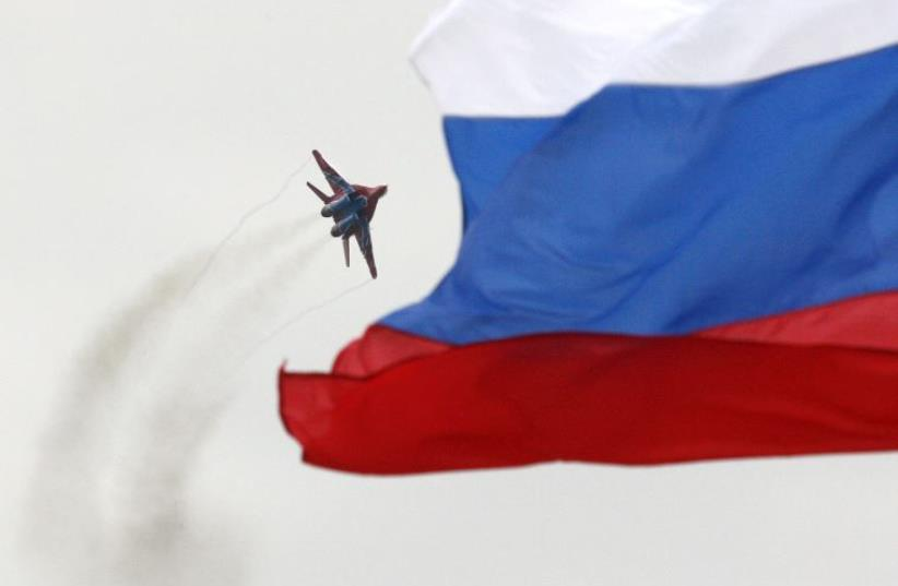 A MiG-29 fighter jet performs a manoeuvre as the Russian national flag flies in the foreground (photo credit: REUTERS)