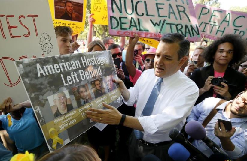 US Republican presidential candidate Senator Ted Cruz shows off a poster of Americans held in Iran as he talks with counter-demonstrators and the media about the Iran nuclear deal (photo credit: REUTERS/JIM BOURG)