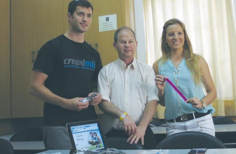 ASSAF LUXEMBOURG (left), CEO of Crowdmii, Eli Gorodezer, the head of MyMDband, and Magi Rozinger-Gasiorowsky, from the Helping Hand Coalition (photo credit: Courtesy)
