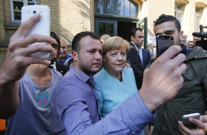 Migrants from Syria and Iraq take selfies with German Chancellor Angela Merkel outside a refugee camp near the Federal Office for Migration and Refugees after their registration at Berlin's Spandau district, Germany, September 10, 2015 (photo credit: REUTERS)