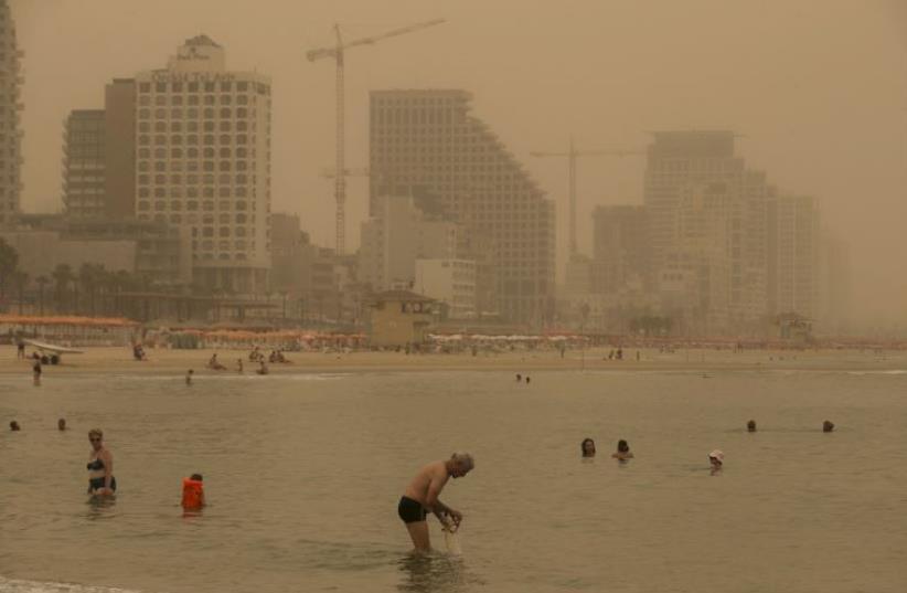 Beachgoers bath at the Mediterranean Sea during a sandstorm in Tel Aviv (photo credit: REUTERS)